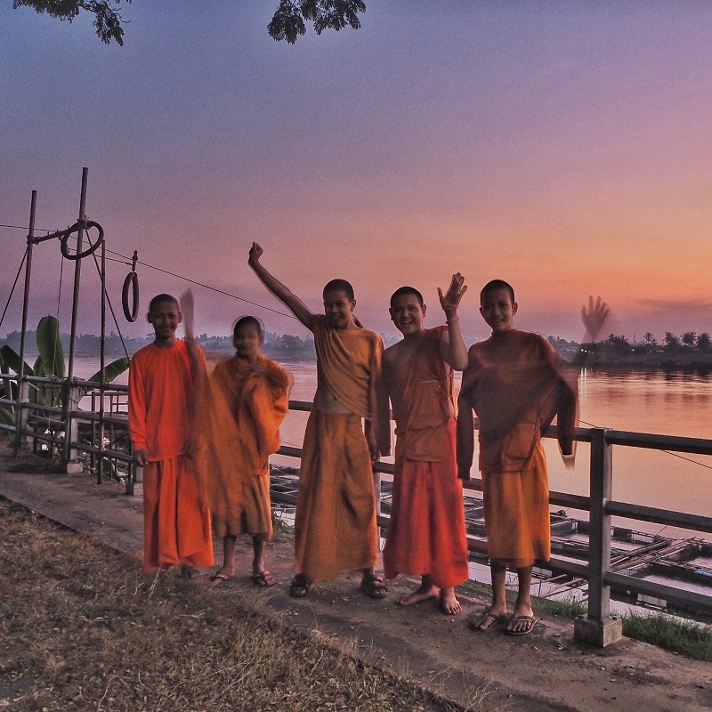 young buddhist monks waving